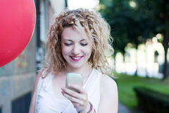 Curly blond girl with big red ballon on the phone Royalty Free Stock Photography