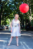 Curly blond girl with big red ballon Stock Photo