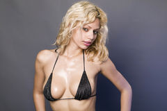 Curly Blond Girl In Black Bikini stock images