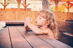 Curly blond girl eats a delicious plum outdoors. Stock Photo