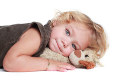 Curly blond girl hugging toy Stock Images