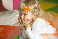 A curly-haired girl on a playground.. A curly blond little girl with a beautiful hairgrip on the head is sitting and thinking about something on a playground Royalty Free Stock Photos