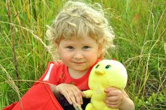 A baby girl in a bag. A curly blonde baby girl sits in a red bag, holding a toy chicken Royalty Free Stock Photography
