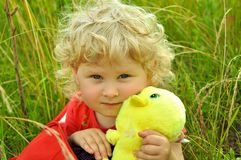 A baby girl in a bag. A curly blonde baby girl sits in a red bag, holding a toy chicken Stock Photography