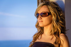 Curly blonde girl with black top and sunglasses Stock Photos