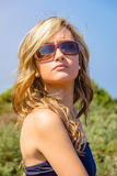 Curly blonde girl with black top and sunglasses Stock Photo