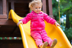 Curly blonde girl sliding at playground Royalty Free Stock Photo