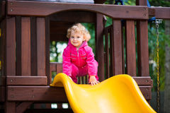 Curly blonde girl sliding at playground Stock Photos