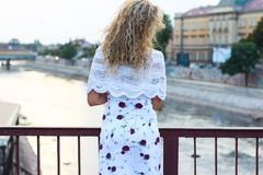 Curly Blonde Girl Standing on the Bridge and Holding a White Sca. Rf Stock Images