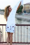 Curly Blonde Girl Standing on the Bridge and Waving With a White. Scarf Royalty Free Stock Photos