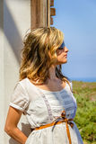 Curly blonde girl with white dress and sunglasses Stock Images