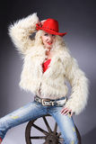 Curly blonde in a red hat. And white fluffy fur coat. A girl sits on an old wooden wheel royalty free stock photo