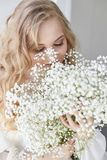 Curly blonde romantic look, beautiful eyes. White wildflowers in hands. Girl white light dress and curly hair, portrait of woman royalty free stock photography
