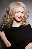Curly blonde woman holding her curl and touching hair by hands. Posing at camera and sensual smiling. Wearing in black blouse with Royalty Free Stock Photo