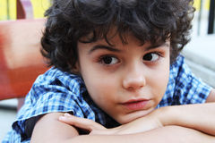 Curly boy. Close portrait of an attractive little boy with blue shirt Royalty Free Stock Photography
