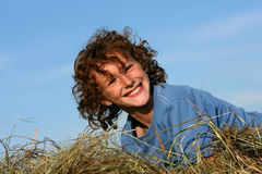 Curly boy. On the haycock Stock Photography