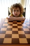 Curly Boy behind sun. Curly boy seat on empty Chess board stock photography