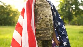 Curly boy in camouflage uniform stands covered by the American flag and smiles. Bottom-up view. Independence day usa.  stock video
