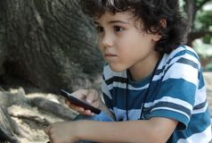 Curly boy with cellphone Stock Photo