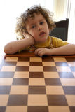 Curly Boy & Chess. Curly boy seat & Chess board royalty free stock image