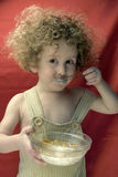 Curly Boy with corn flakes. Curly boy enjoy his breakfast royalty free stock photos
