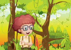 A curly boy in the forest near the trees Royalty Free Stock Photo