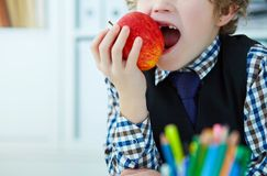 Curly Caucasian boy with missing front teeth trying to bite an apple. Curly boy with missing front teeth trying to bite an apple Stock Photo
