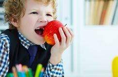 Curly boy with missing front teeth trying to bite an apple. Curly Caucasian boy with missing front teeth trying to bite an apple Royalty Free Stock Image