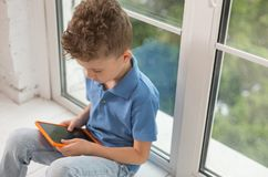 Curly boy in polo shirt playing games on laptop. Laptop games. Handsome curly boy in stylish polo shirt playing funny games on laptop while sitting near window Royalty Free Stock Image