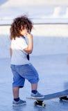 Curly boy riding a skateboard Stock Image
