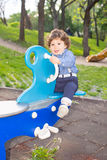 Curly boy  on seesaw in park Stock Image