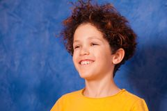 Curly boy smiling and looking into the distance. Portrait of preteen curly boy smiling and looking into the distance against background with copy-space Royalty Free Stock Photography