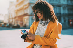 Curly brazilian woman using retro camera. Attractive curly Brazilian woman with vintage camera on street of Lisbon, adult white stylish lady in sweater and Royalty Free Stock Photos