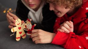 Curly brother and sister in Christmas pajamas play with figures to decorate the Christmas tree. Family holiday Christmas stock footage