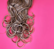 Curly brown hair over pink Royalty Free Stock Photos