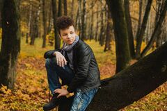 Curly brown-haired boy with a mohawk hairstyle in a leather jacket against the background of an autumn forest
