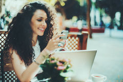 Curly brunette girl in cafe with smartphone and laptop Stock Photo