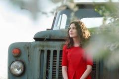 Curly brunette girl in crimson red dress during springtime vintage travel Stock Images