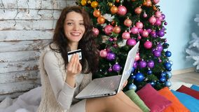 Curly brunette holding credit card for online shopping. female buyer buying christmas gift on internet. new year holiday. Merry xmas celebration stock video