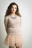 Curly Brunette In Pink Mini Skirt. Portrait of a beautiful brunette woman with curly hair wearing a tutu like pink mini skirt against a white background. Also Stock Image