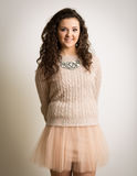 Curly Brunette In Pink Mini Skirt. Portrait of a beautiful brunette woman with curly hair wearing a tutu like pink mini skirt against a white background. Also Royalty Free Stock Photo