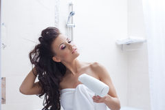 Curly brunette posing with hairdryer Royalty Free Stock Images