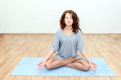 Curly brunette sitting in a lotus position on the floor Royalty Free Stock Photography