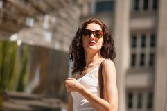 Curly brunette in sunglasses. Arrogant and confident look. Portrait, Prague, May 28, 2017, near the monument to Hlava stock photos