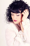 Curly brunette woman in a white blouse Royalty Free Stock Photos