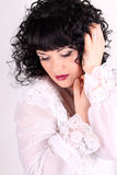 Curly brunette woman in a white blouse Royalty Free Stock Image