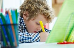 Curly Caucasian boy sitting at the desk at home and doing his homework. School, children, education concept. Close-up portrait of curly Caucasian little boy Stock Photo
