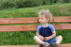 Curly child on a bench Stock Photography