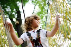 A curly child in climbing safety. Equipment in a tree house or in a rope park climbs the rope. Active children Royalty Free Stock Images