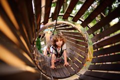A curly child in climbing safety. Equipment in a tree house or in a rope park climbs the rope. Active children Stock Images